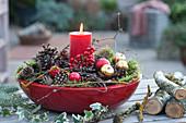 Kerze weihnachtlich geschmückt in roter Schale