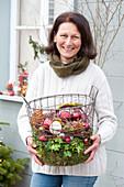Frau bringt Drahtkorb mit Christbaumkugeln, Zapfen und Moos