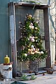 Stilisierter Tannenbaum aus Zweigen, Kugeln und Lichterkette
