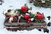 Holzkiste mit Kerzen und Christbaumschmuck im Schnee