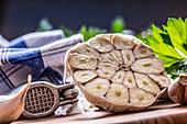 Halbierte Knoblauchknolle und Knoblauchpresse