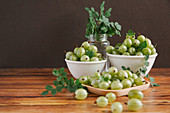 Gooseberries in small bowls on a wooden table