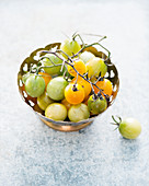 Green and yellow cherry tomatoes in a small bowl