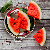 Watermelon slices on a silver tray and a wooden background