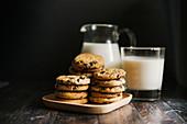 Chocolate Chip Cookies, dahinter Milch im Glas und Krug