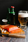 A fresh salmon fillet on a wooden board and a glass of beer