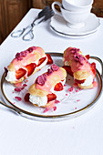 Eclairs with strawberries and cream