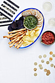 Chips, crackers and breadsticks with dips for New Year's Eve