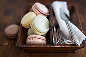 Various colourful macarons with cutlery and napkins in a wooden box