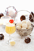 A glass of eggnog, and white egg liqueur chocolate truffles in a silver bowl