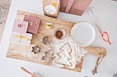 Christmas presents and baking utensils on wooden board seen from above