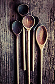 Several old wooden spoons on a wooden background