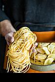Mann hält selbstgemachte Pasta