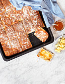 Homebaked bread on a baking sheet with butter and orange marmalade