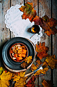 Chicken curry with pumpkin, a cup of tea and autumn leaves
