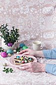 Woman holding plate with Mazurek (No bake Polish Easter cake)