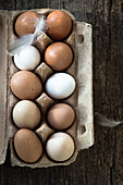 Brown and white chicken eggs in an egg carton