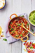 Vegetarian bean chilli topped with spring onions, chilli and corinader, served with tortilla chips with raw onion and fresh chilli and guacamole