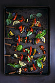 Gemüsespiesse mit Basilikum auf Ofenblech (Aufsicht)