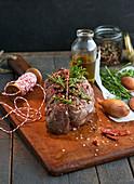 Rohes, geschnürtes Rinderfilet in der Zubereitung mit Kräutern und Zutaten