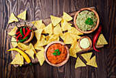 Mexican nachos with guacamole, salsa and cheese dip in wooden bowls on dark background