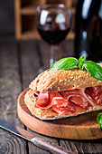 Close up ciabatta sandwich with jamon serrano and basil, on wooden background