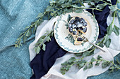 A little blackberries tarte on a brocante plate on a green cloth with green leaves