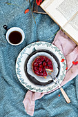 Raspberries cake with a cupo of tea and a book