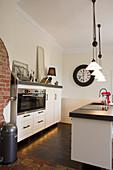 Weiße, halbhohe Einbauküche und Kücheninsel, darüber Pendelleuchten