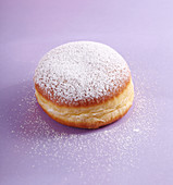 A carnival doughnut with icing sugar