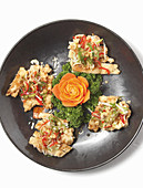 Fish cutlets garnished with parsley and a carved carrot flower (Asia)