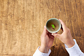 A woman holding a cup of green tea
