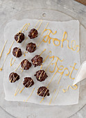 Cappuccino pralines on paper decorated with the words 'Frohes Fest'