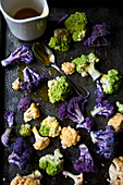 White cauliflower, purple cauliflower and romanesco broccoli with turmeric oil on an antique baking sheet