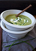 Two bowls stacked, one with asparagus soup, topped with creme fraiche and chopped chives