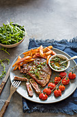 Steak with chimichurri sauce, chips, rocket and grilled tomatoes
