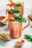 Blood orange Moscow mule alcohol cocktails with fresh mint leaves and ice in copper mugs over white marble background