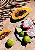 Frische tropische Früchte auf Steinuntergrund (Aufsicht)