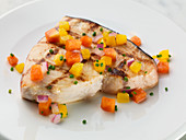 Grilled swordfish steak with diced vegetables (close-up)