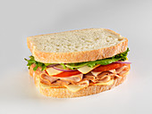A sandwich with turkey breast, tomatoes, Munster cheese and salad