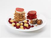 Süsse und pikante Snacks auf Teller: Cracker, Wurst, Trockenfrüchte und Konfekt