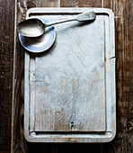 A chopping board with a spoon and a small plate