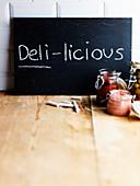 Kreidetafel mit Aufschrift Deli-licious und verschiedene Einmachgläser