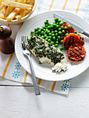 Fish in a herb coat with grilled tomatoes, peas and French fries