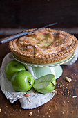 Apple pie on a cake stand, and fresh green apples