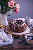 Bundt cake with lemon glaze drizzle and blueberries on a rustic wooden table