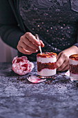 Frau isst Parfait-Schichtdessert mit Erdnussbutter und Chia-Himbeermarmelade