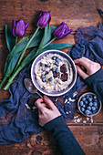 Woman eating semolina porridge topped with blueberries, chocolate and almonds