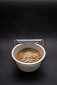 Asian rice noodle soup with vegetables in a plastic cup