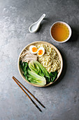 Asian dish with udon noodles with boiled egg, mushrooms, boc choy, broth in ceramic bowl